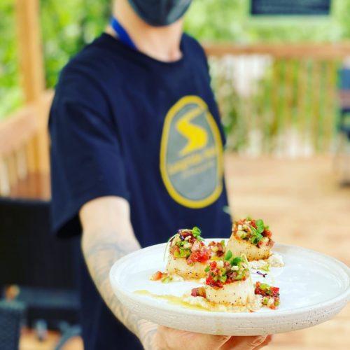 Serveur présente un plat sur la terrasse